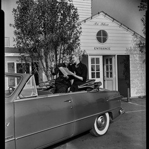 Two women posed in a car in front of the Farmers Market, ...