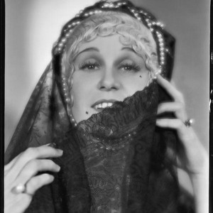 Peggy Hamilton modeling a headband with braided pearls and a veil, 1931