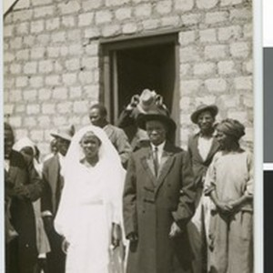 Bridal couple and others in front of a stone building, South Africa