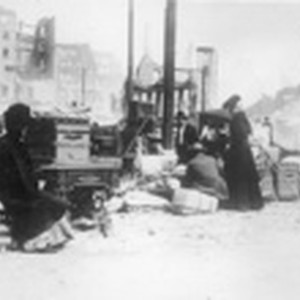[Refugees with belongings in street]