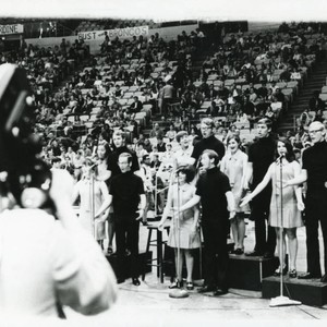 TV cameraman recording the audience and singers in the Firestone Fieldhouse. Sign: ...