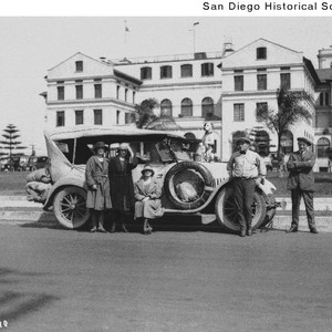 Three women and two men around an automobile parked in front of ...