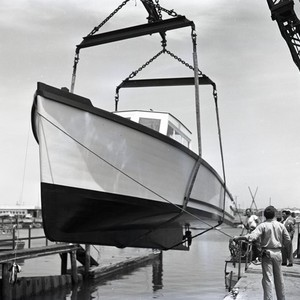 Unidentified boat lifted up at a dock in Newport Harbor, Newport Beach, ...