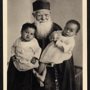 Missionary father holding two infants on his lap, Madagascar, ca.1920-1940