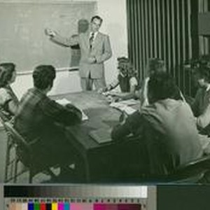 Students seated at a table looking at a chalkboard