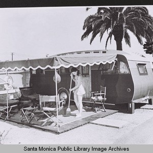 Woman sweeps the covered patio area outside her trailer in Santa Monica, ...