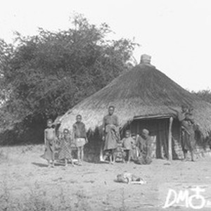 Group of African people standing in front of a hut, Makulane, Mozambique, ...
