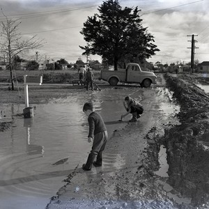 Children playing in flood water caused by a storm, Newport Beach, California: ...