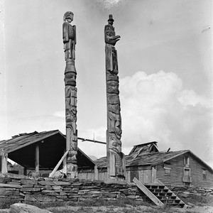 Eagle and eagle and man totems (man is wearing stovetop hat), Alaska. ...