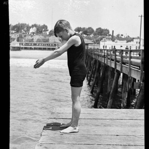 Boy in diving pose at end of North Beach Bath House Pier, ...