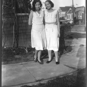 Muriel Taylor and young woman standing on walkway next to house
