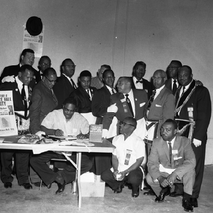 "George Holbert at book signing table, man holding up placard ""The Story ..."