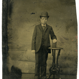 Tintype of a boy standing wearing a dark colored suit and a ...