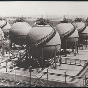 Exterior view of an unidentified oil refinery, showing rows of spherical tanks, ...