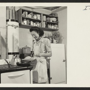 Mrs. Thomas Taneichi Kamikawa is preparing supper in the kitchen of the ...