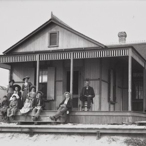 Photograph of family in front of beach cottage