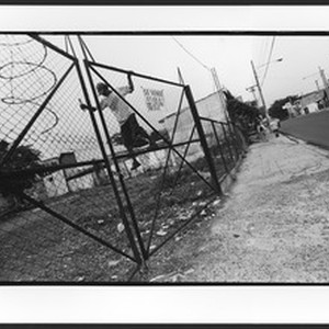 Young man of Hispanic origin jumping over the fence of a vacant ...
