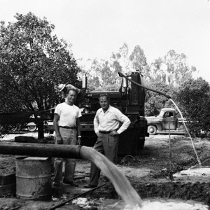 Tustin Water Works superintendent, Walter Rawlings, and Earl Rowenhorst watch water pour ...