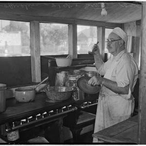 Cook stands with a ladle in the kitchen of a cooperative in ...