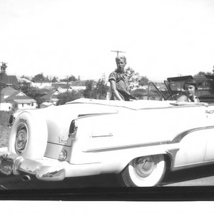 Group of young people with a light colored Lincoln Continental convertible car ...