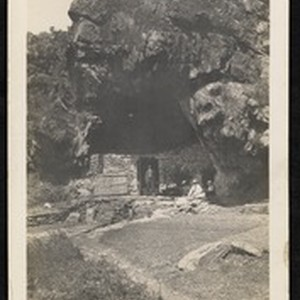 Man standing in the doorway of a walled-in cave, China, ca.1910-1915