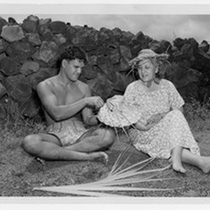 Man showing a woman a woven coconut palm hat, Hawaii, ca. 1947