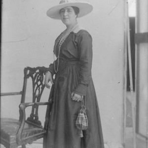 Photo portrait of a woman, standing next to a chair, wearing a ...