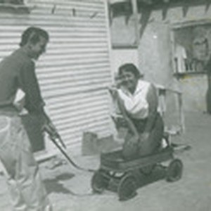 Man pulling his sister-in-law in a wagon, East Los Angeles, California