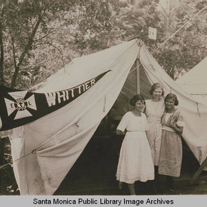 "Young women stand in front of a tent ""Whittier""at the Institute Camp, ..."