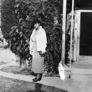 Woman in front of family home
