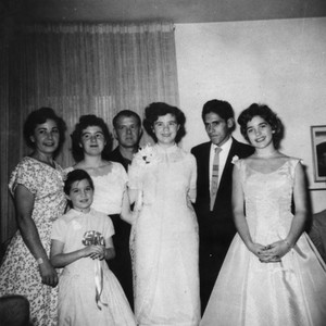Mexican American groom with bride and family