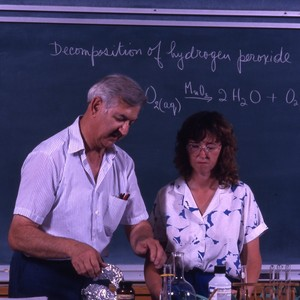 Unidentified professor with a student in a science lab ,conducting an experiment.
