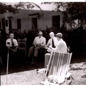 Max Poehlmann, Nathan Thompson and two unidentified men sitting in the backyard ...