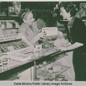 Two women at a cosmetics counter featuring Helena Rubinstein lipstick in the ...