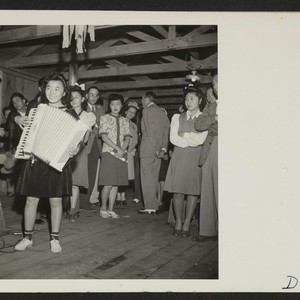 Manzanar, California--A young evacuee of Japanese ancestry entertains on an accordion at ...