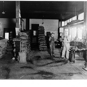 Men standing beside burlap bags and scales inside an unknown warehouse