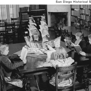 Children sitting at a table reading books in a San Diego State ...