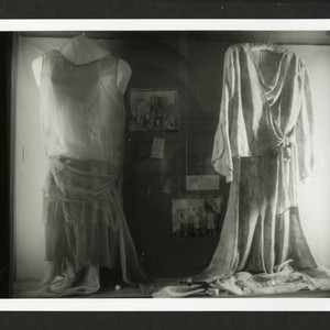 Two dresses hanging in a glass cabinet, Denison Library, Scripps College