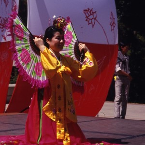 Woman in Traditional Costume Dancing with Fan