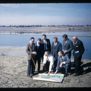 Rowing founders pose with map near water