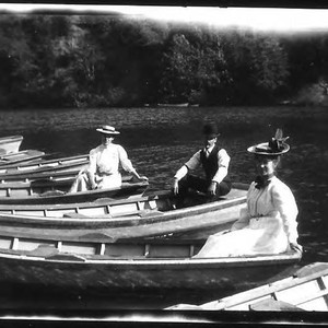 Three people in three separate boats--2 women and 1 man--among other empty ...