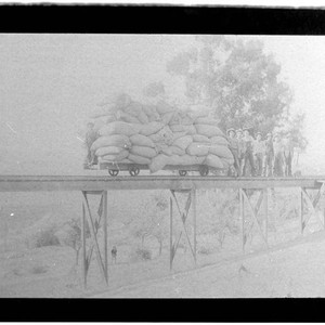 Men standing on a railroad trestle next to a rail car piled ...