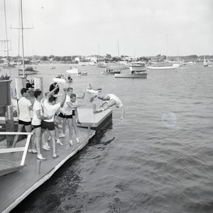 Crew racing team playing on dock, Newport Beach, California: Photograph