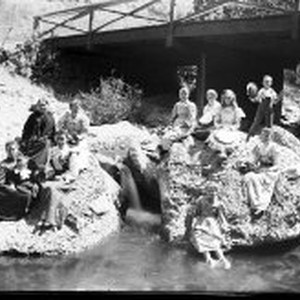 Group outdoors on rocks, with bridge behind