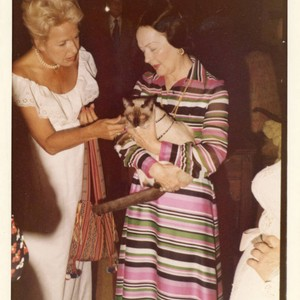 Mrs. Alice Tyler holding a Siamese cat and talking with a guest ...