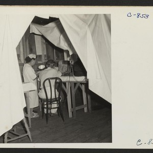 Manzanar, Calif.--Making an examination of an evacuee patient are Dr. Takahashi, Ear, ...