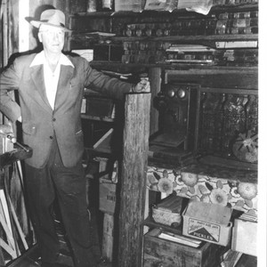 Unidentified man standing in front of shelves of artifacts, Petaluma, California, about ...