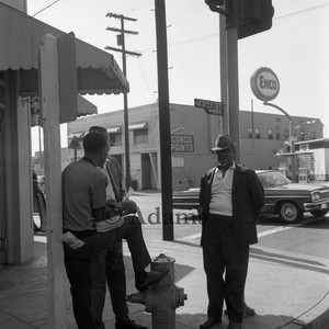 Three men gather at 43rd Street, Los Angeles, 1971