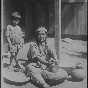 Paiute woman grinding meal on stone mortar (or metate), using stone pestle