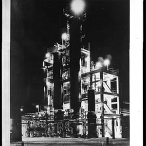 Exterior view of Shell Oil Company refinery at night, ca.1940